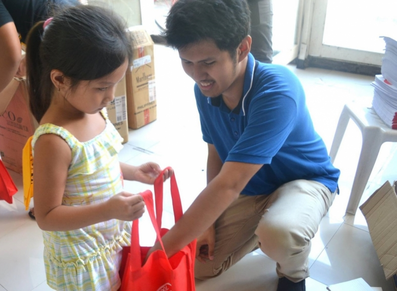 A KAIROS band member gives school supplies to a child during the Off-the-Street, On-to-School project (Photo by GABAY)